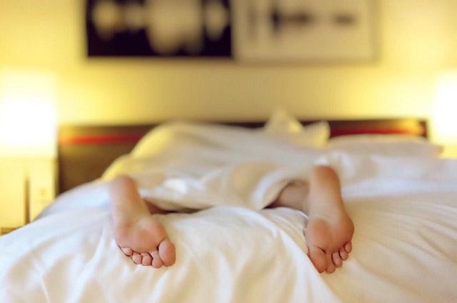 Osoba leží v posteli, nohy.jpg