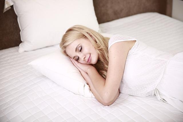 Žena s blond vlasmi spí pokojne na posteli.jpg